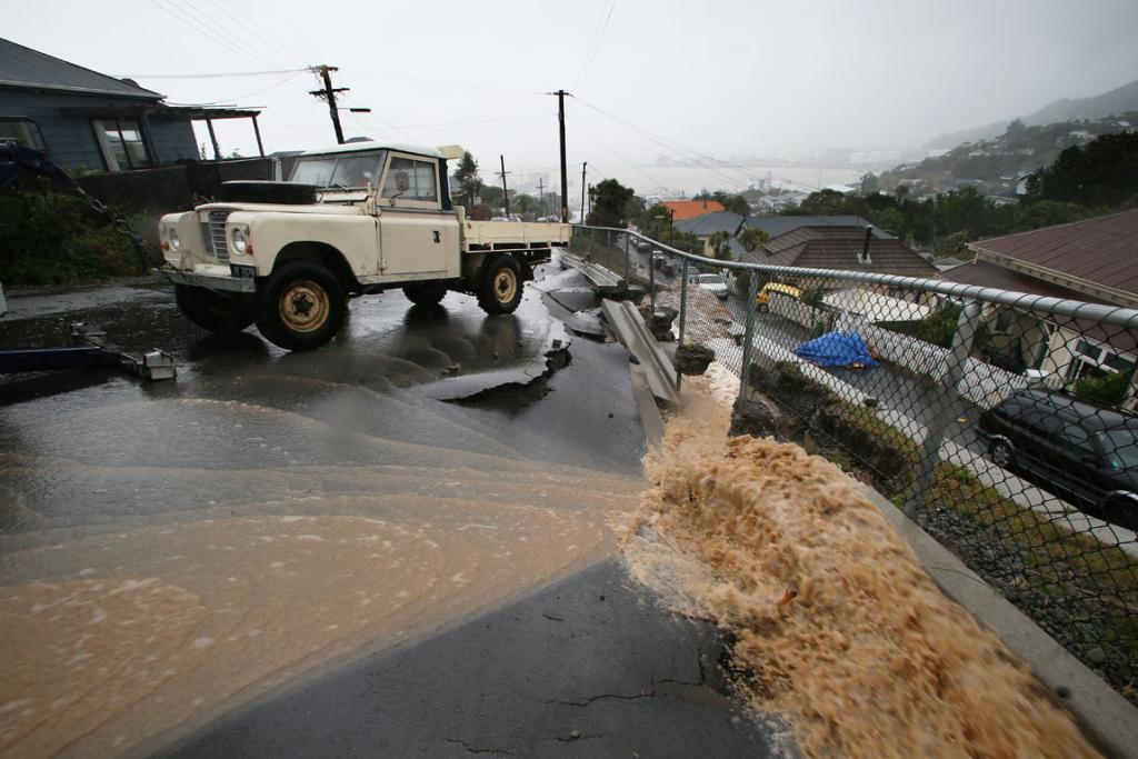 Pete Sheild, in his truck is rescued on Canterbury Street in Lyttleton after a river of flood water eroded the side of the road.