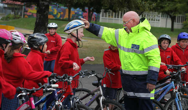 Mahaliya Tito gets her helmet checked by school community officer Chris Wiltshire at Temuka Primary school as part of safe cycling education.