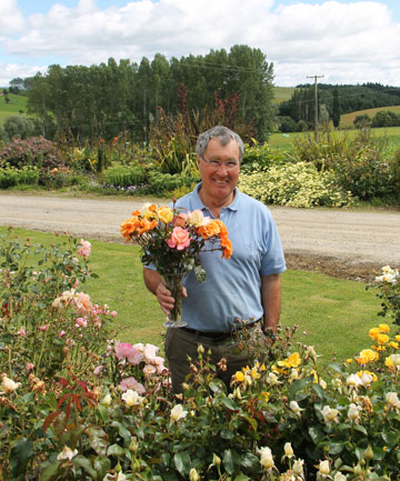 Rose breeder David Benny with some of his blooms.