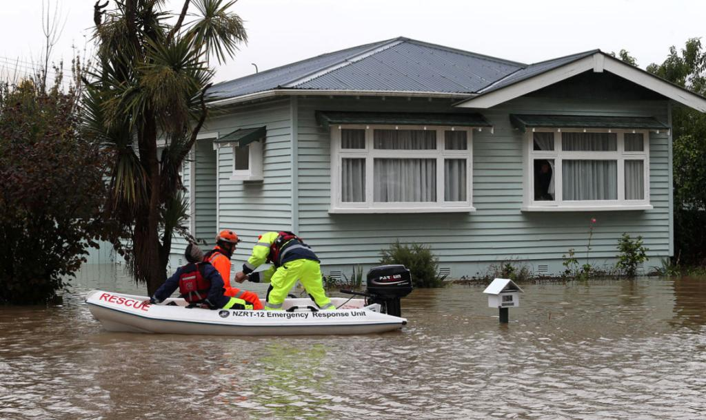 A resident looks out her window at a rescue team starting their engine on the Heathcote River flood waters on Riverlaw Terrace.