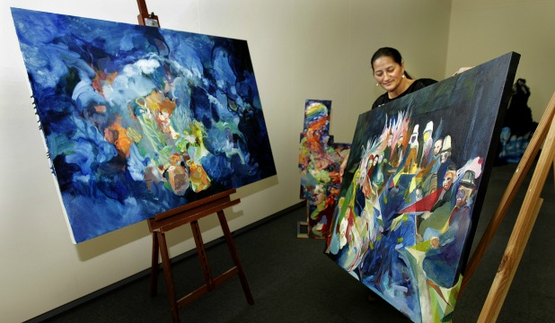 Te Ao Pritchard, of Te Manawa, sets up artworks by Kirsty Porter