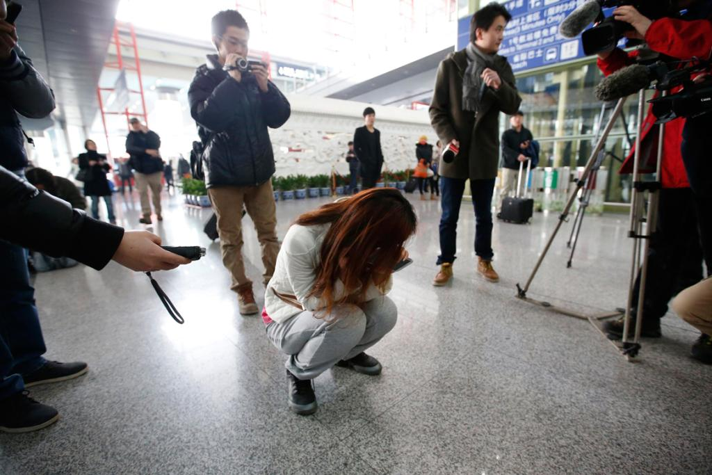Journalists attempt to interview a woman who is the relative of a passenger on Malaysia Airlines flight MH370, as she crouches on the floor crying, at the Beijing Capital International Airport.