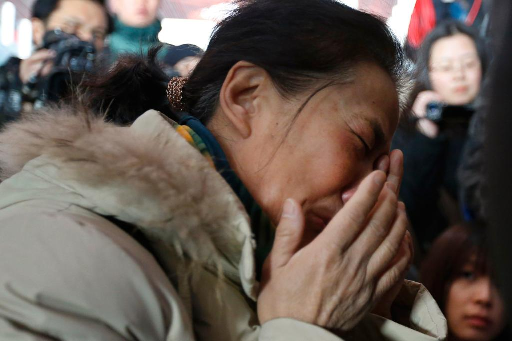 A relative of a passenger onboard Malaysia Airlines flight MH370 cries, surrounded by journalists, at the Beijing Capital International Airport on March 8, 2014.