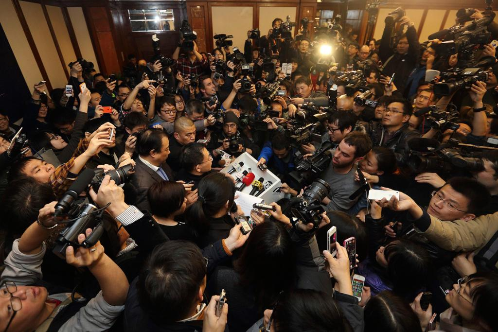 A spokesman (centre) of Malaysia Airlines is surrounded by journalists as he gives a briefing about Malaysia Airlines flight MH370, at a hotel in Beijing March 8, 2014.