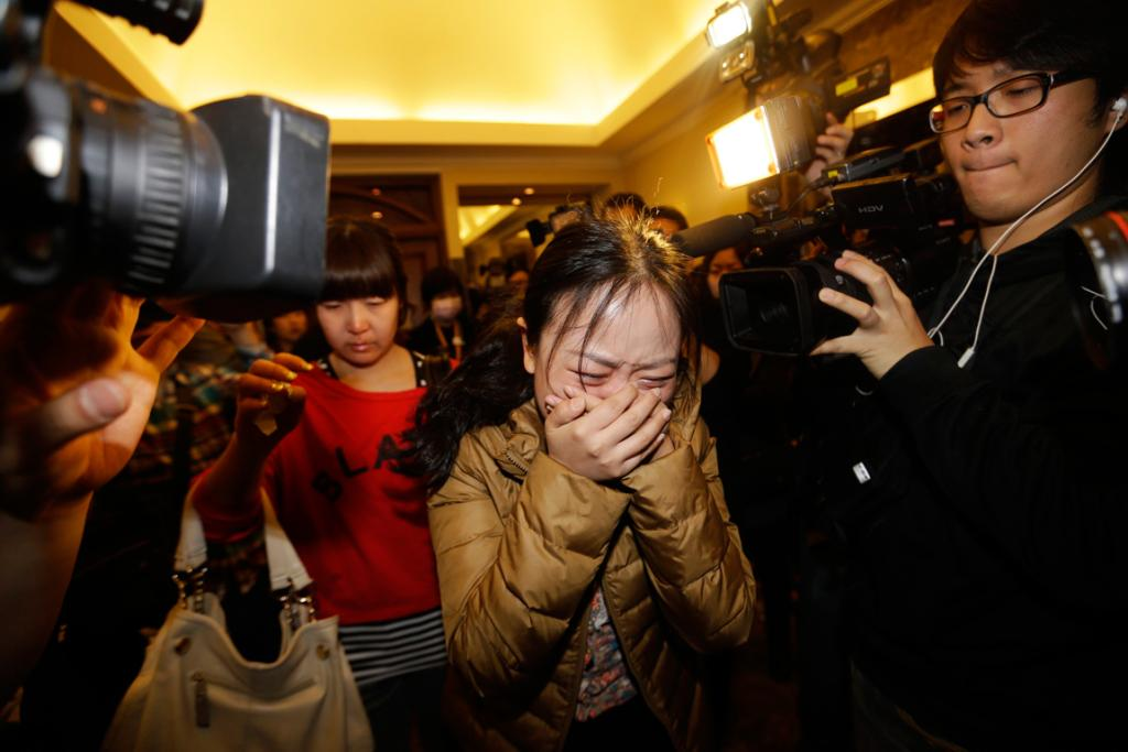 A relative (front) of a passenger of Malaysia Airlines flight MH370 cries as she walks past journalists at a hotel in Beijing March 9, 2014. The Malaysia Airlines Boeing 777-200ER aircraft carrying 227 passengers and 12 crew was presumed to have crashed off the Vietnamese coast on Saturday.