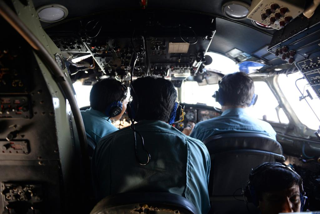Vietnamese Air Force officers sit in the cockpit of a search and rescue aircraft as they fly over the search area for a missing Malaysia Airlines plane.