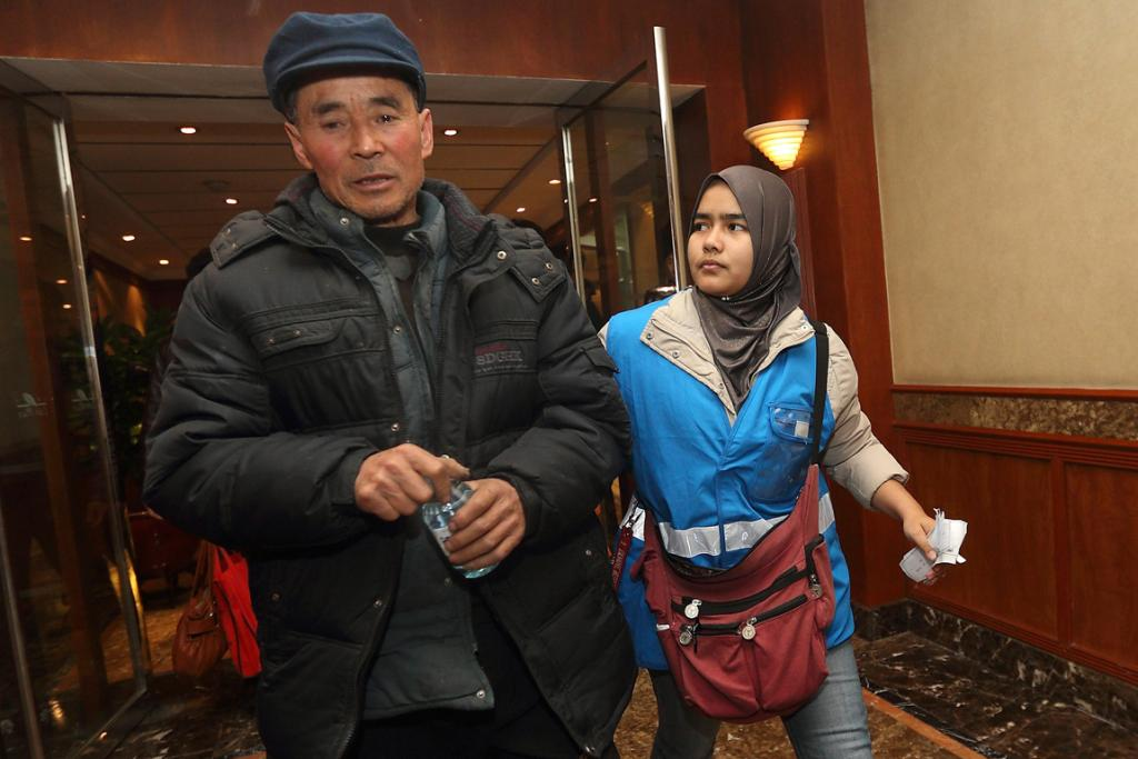 A relative (left) of a passenger of Malaysia Airlines flight MH370 is escorted by a caregiver from Malaysia Airlines as they walk in a corridor at a hotel in Beijing.