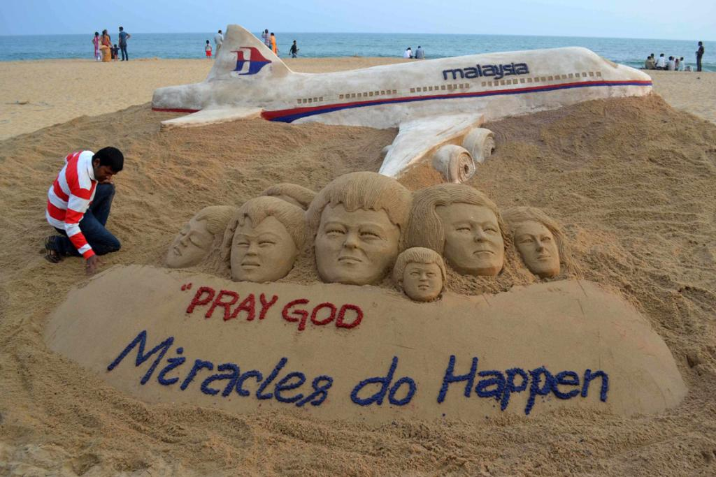 Indian sand artist Sudarshan Patnaik applies the final touches to a sand art sculpture he created wishing for the well being of the passengers of Malaysian Airlines flight MH370, on a beach in Puri, in the eastern Indian state of Odisha.