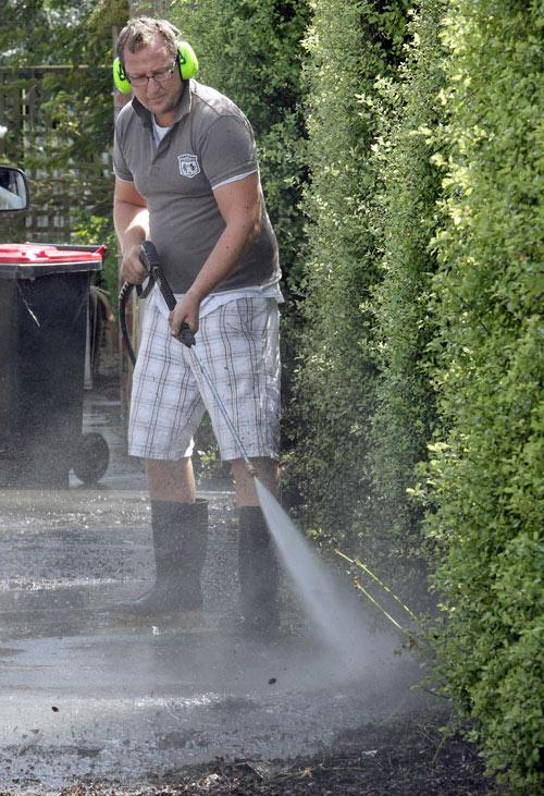 Post Flooding in Christchurch, Carrick Street in Saint Albans. James Adams cleaning up his drive.