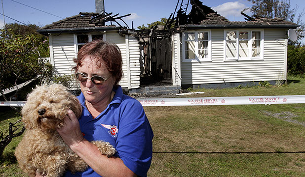 RESCUE PUP: Neighbour Kathryn Collins with her dog which raised the alarm when this Marton house went up in flames.