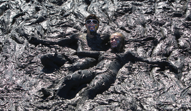 MUD BATH: Muddy buddies Dominick Johnson, left, and Cambria Doyle lay in a mud bog to rest after getting stuck on their way around the course during the Sport Tasman Muddy Buddy.