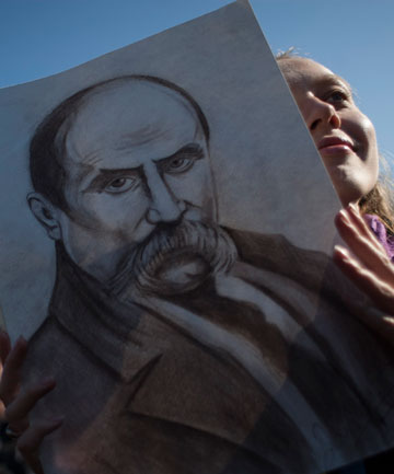 'LITERARY FATHER': A sketch of Taras Shevchenko is carried by a woman in Kiev's Independence Square on the 200th anniversary of the Ukrainian's birth.
