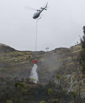 WATER DROP: A helicopter uses a monsoon bucket to douse hotspots left by the blaze.