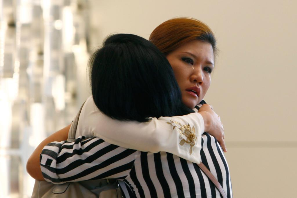 Relatives of a passenger onboard the missing Malaysia Airlines flight MH370 cry inside a hotel they are staying, in Putrajaya. China has urged Malaysia to step up the search for the jetliner that went missing with 239 people on board, about two-thirds of them Chinese, and said it has sent security agents to help with an investigation into the misuse of passports.