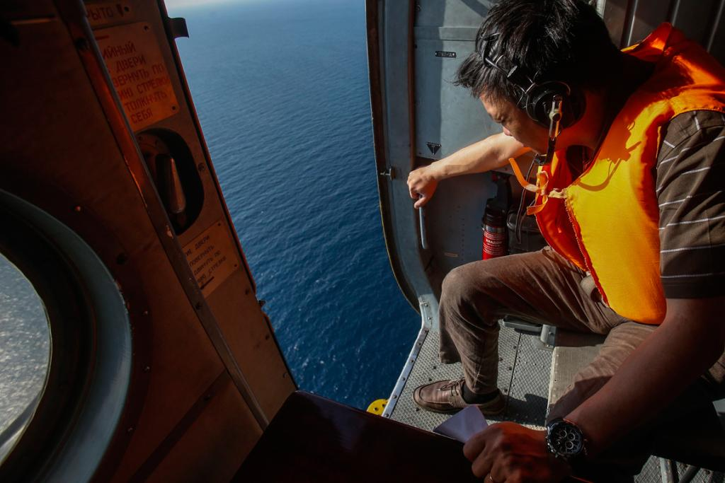 An officer looks out of a helicopter during a mission to find the Malaysia Airlines flight MH370 that disappeared from radar screens in the early hours of Saturday, near Tho Chu Island.
