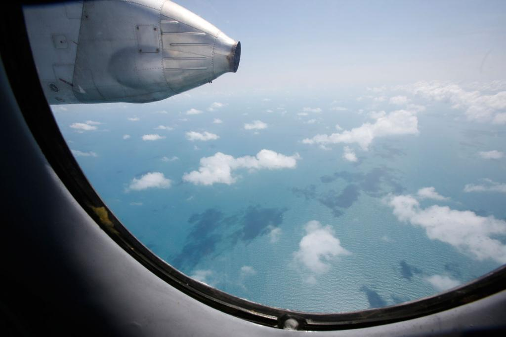 Clouds hover outside the window of a Vietnam Air Force search and rescue aircraft An-26 on a mission to find the missing Malaysia Airlines flight MH370, off Vietnam's Tho Chu island.