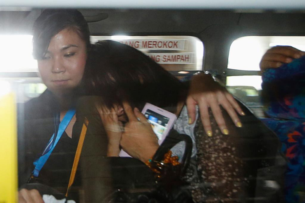 A Chinese relative of a passenger of Malaysia Airlines MH370 is comforted by a staff member of the airport as she shields her face from journalists at Kuala Lumpur International Airport.