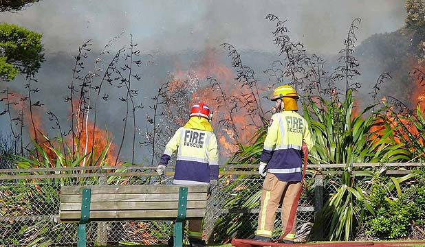 UP IN FLAMES: East Coast Bays firefighters put out a fire in Castor Bay.