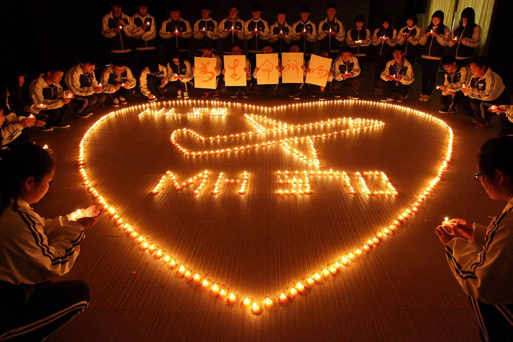 Students from an international school in east China city Zhuji pray for the passengers onboard Malaysia Airlines flight MH370.