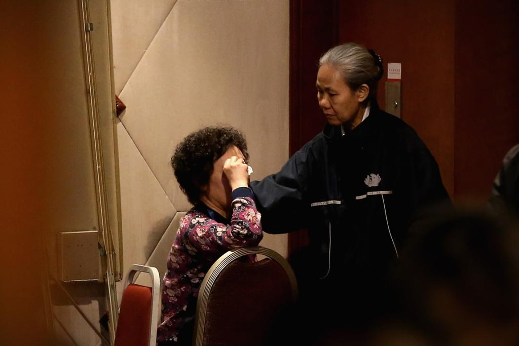A charity worker comforts an emotional relative of a passenger.