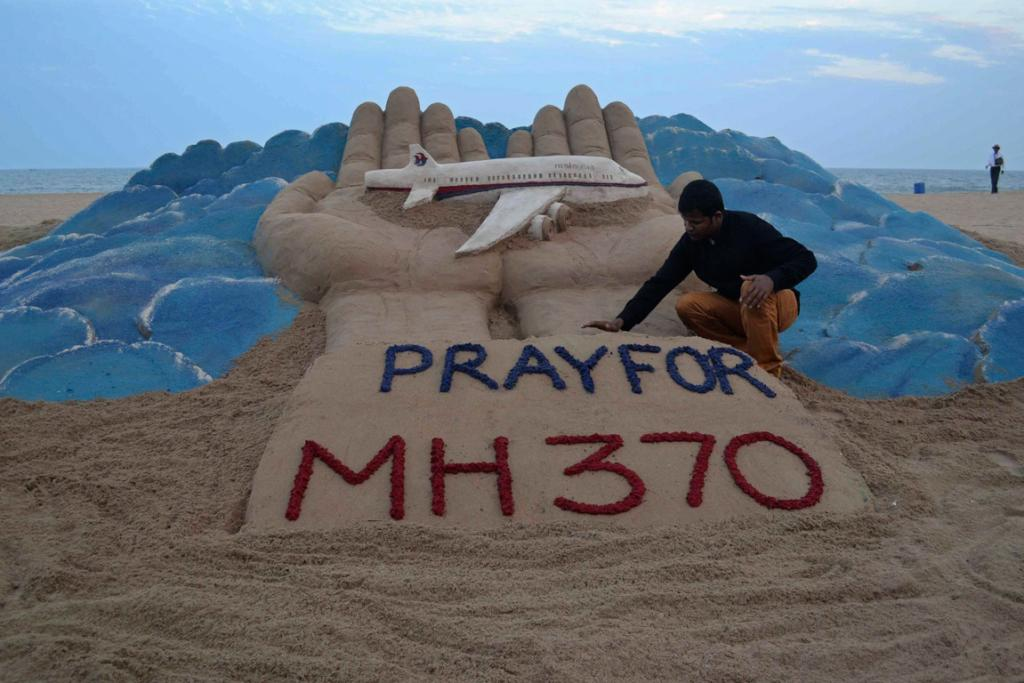 Indian sand artist Sudarshan Pattnaik works on a sand sculpture of missing Malaysia Airlines flight MH370, at golden beach at Puri in the eastern Indian state of Odisha.