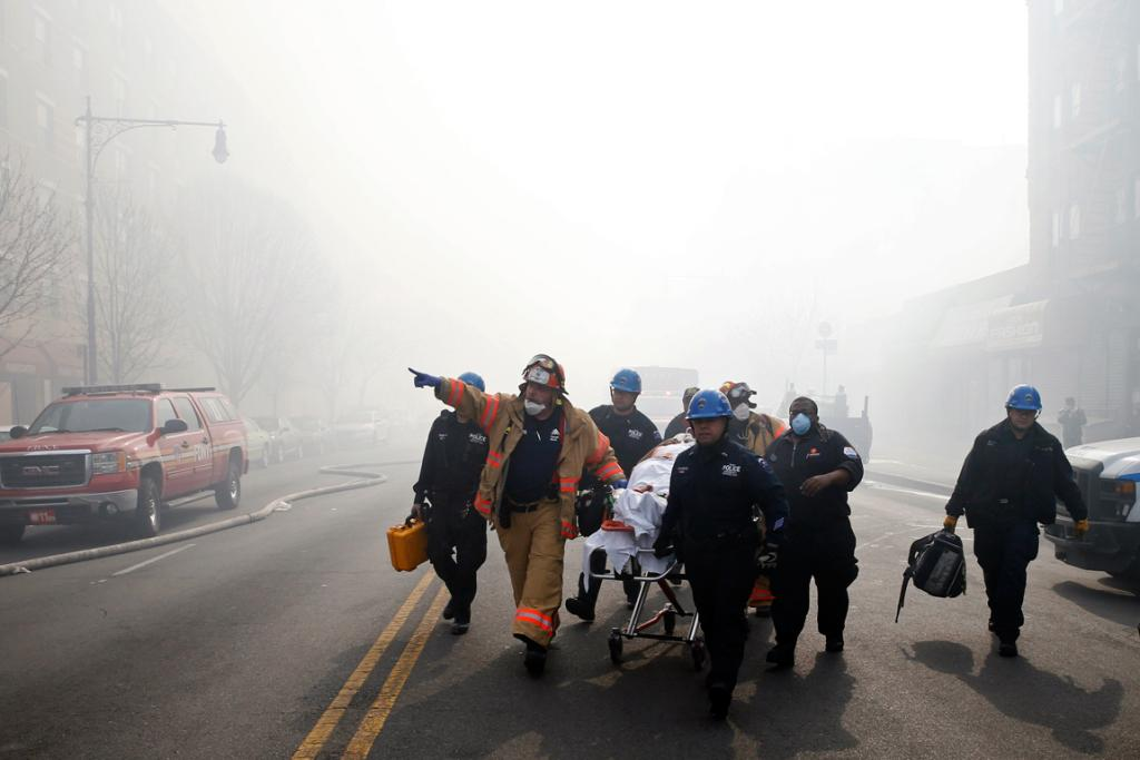 A victim is evacuated by emergency personal near a building explosion in the Harlem section of New York City.