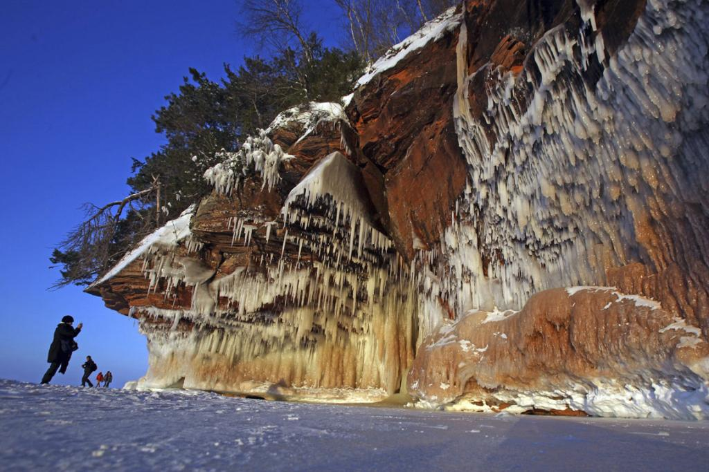A woman photographs ice formations at sunset on a rock face of the Apostle Islands National Lakeshore of Lake Superior, the world's largest freshwater lake, to the sea caves near Cornucopia, Wisconsin, USA.