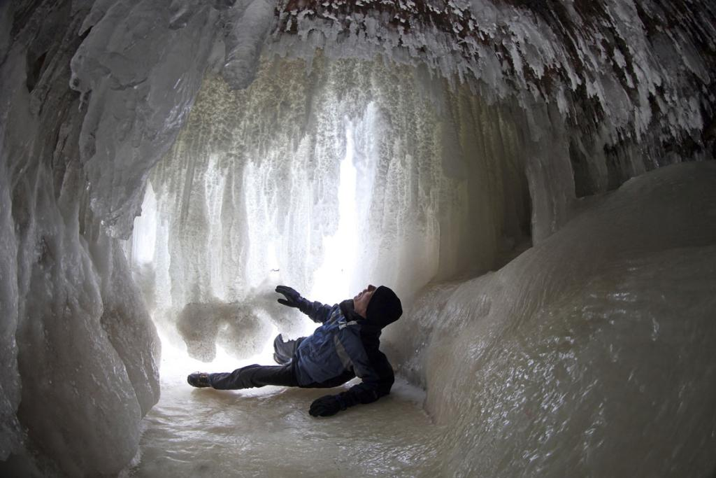 A local examines the ice formations in a sea cave at the Apostle Islands National Lakeshore of Lake Superior near Cornucopia, Wisconsin.