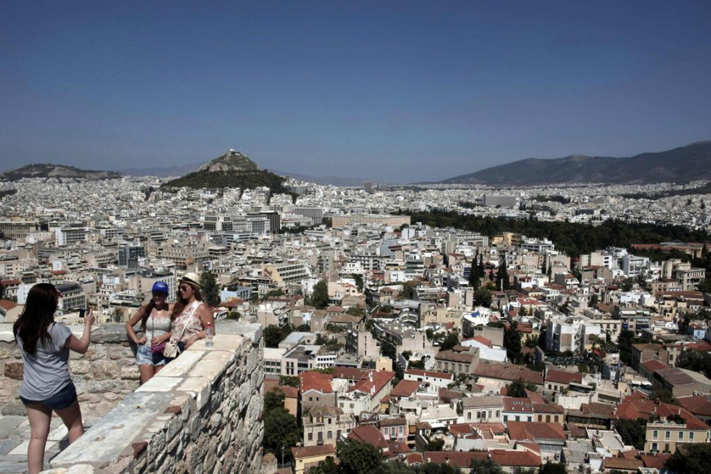 Tourists pose for a photo at the top of the Acropolis hill in Athens.