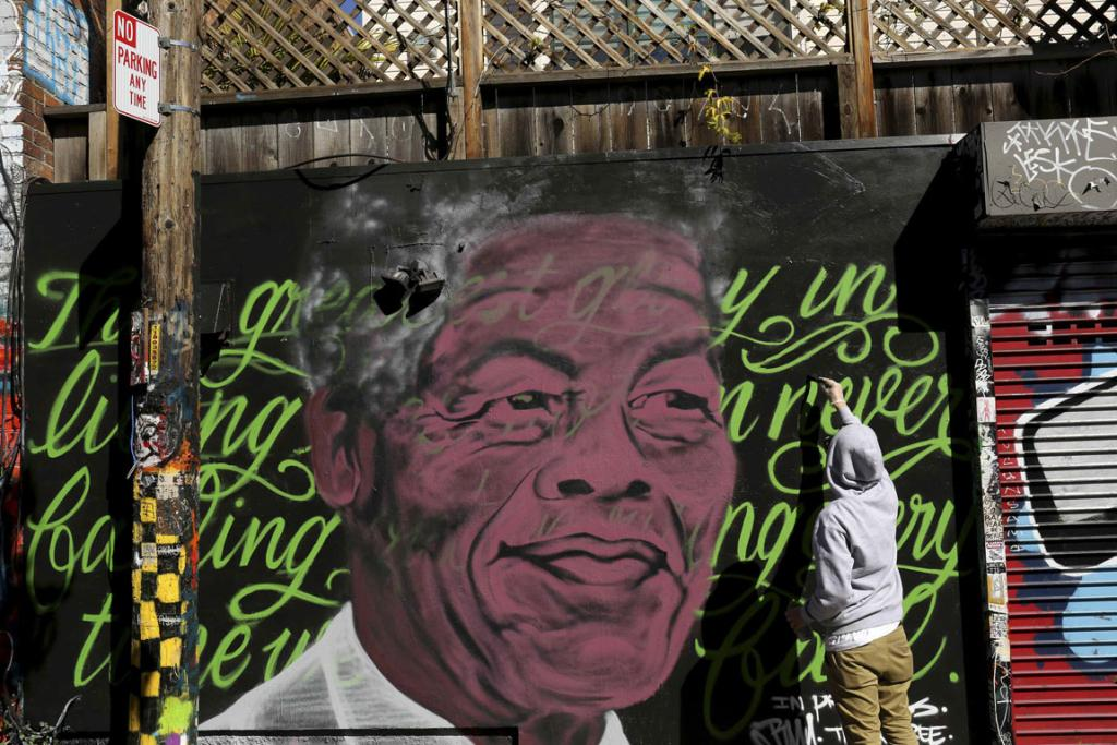 A muralist paints a tribute to Nelson Mandela in Clarion Alley in the Mission neighborhood in San Francisco, California.