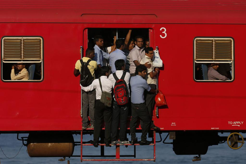 People hang onto a crowded local passenger train as they travel to Colombo, Sri Lanka.