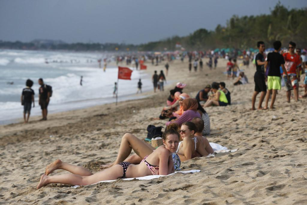 Tourists gather on Kuta beach near Denpasar in Bali.