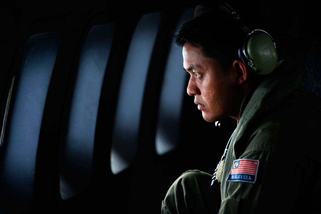 A crew member from the Royal Malaysian Air Force looks through the window of a Malaysian Air Force CN235 aircraft during a Search and Rescue operation to find the missing Malaysia Airlines flight MH370.