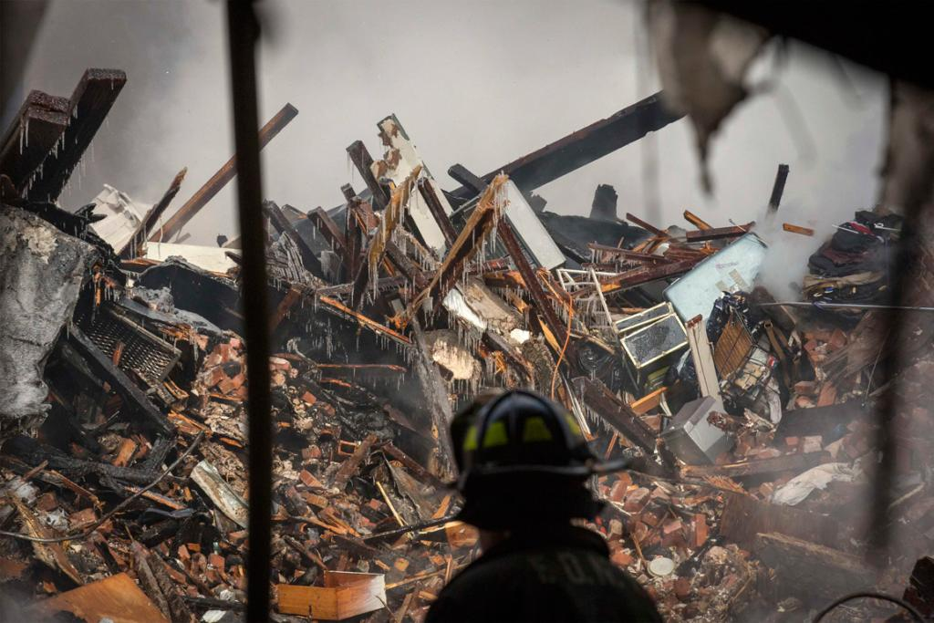 New York City emergency responders search through the rubble at the site of a building explosion in the Harlem section of New York.