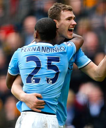 Manchester City's Edin Dzeko celebrates with teammate Fernandinho after scoring his team's second goal against Hull City in the English Premier League.