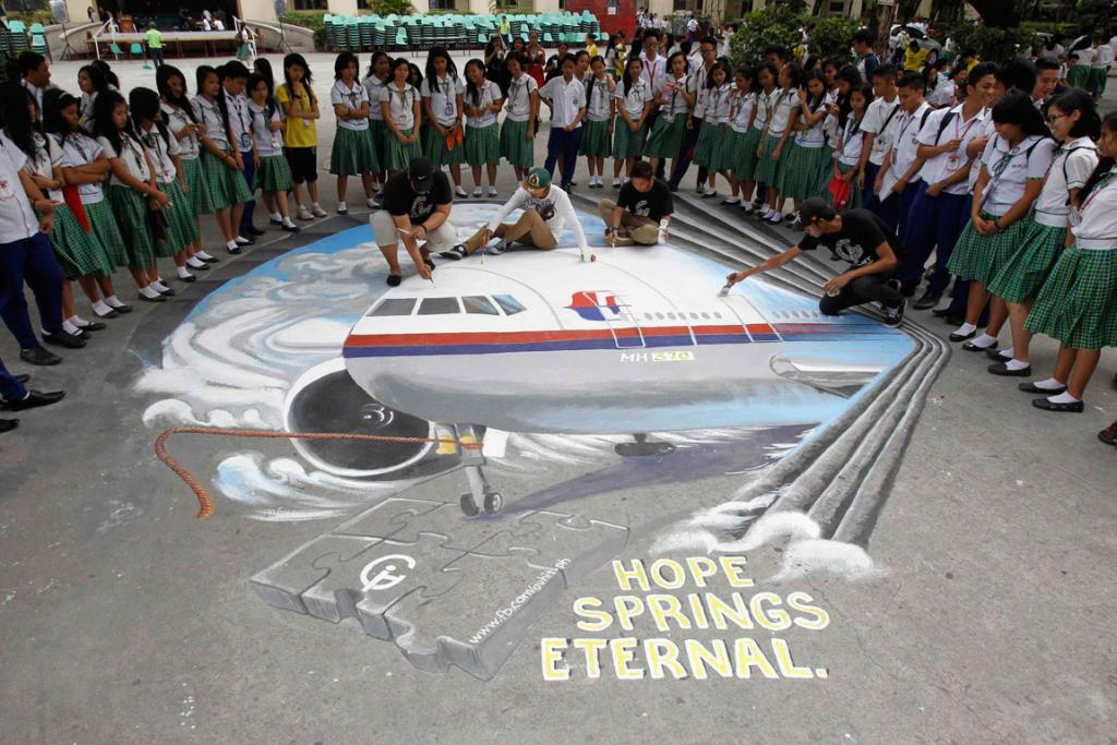 Students watch as a group of artists put the finishing touches to a three dimensional artwork at a school in Makati city, metro Manila. According to the artists, the artwork is their way of expressing sympathy towards the relatives of passengers onboard the missing Boeing 777-200ER.