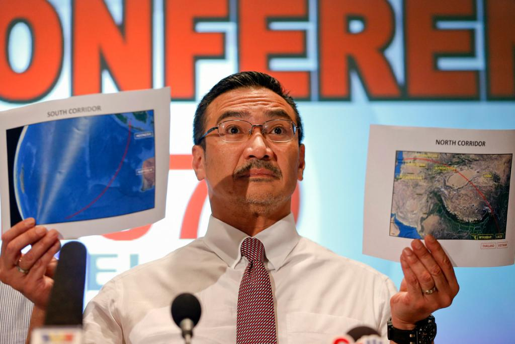 Malaysia's acting Transport Minister Hishammuddin Hussein shows two maps with corridors of the last known possible location of the missing plane.