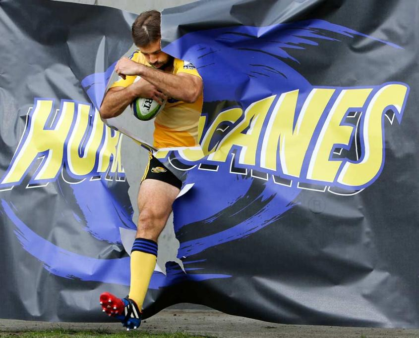 Conrad Smith breaks through a Hurricanes banner as he runs onto the field for his 100th match.