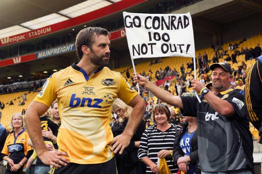 Conrad Smith poses in front of a fan's banner celebrating his 100 Super Rugby matches.