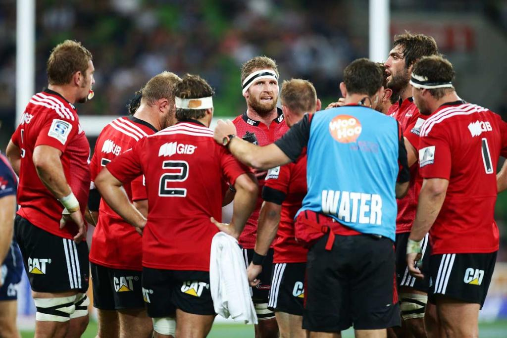 Captain Kieran Read chats to his forward pack during a break against the Rebels.