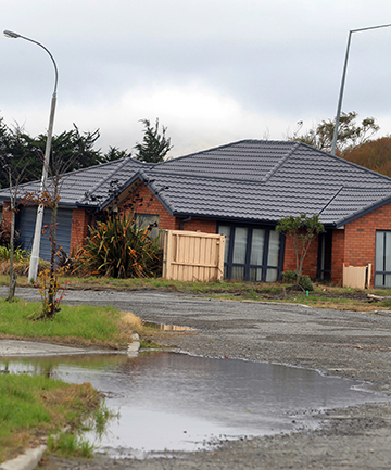 CLEARING THE WAY: About half of the homes in the red-zoned suburb of Bexley in east Christchurch have been demolished. The homes that remain are cracked, warped and filled with silt.