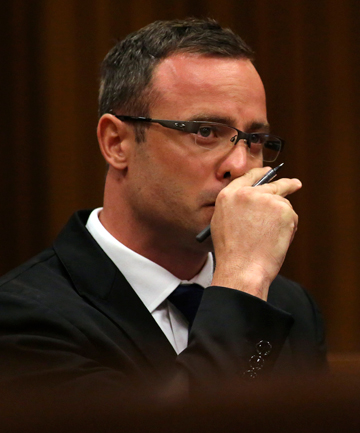 IN COURT: Olympic and Paralympic track star Oscar Pistorius reacts as he sits in the dock during his trial for the murder of his girlfriend Reeva Steenkamp.