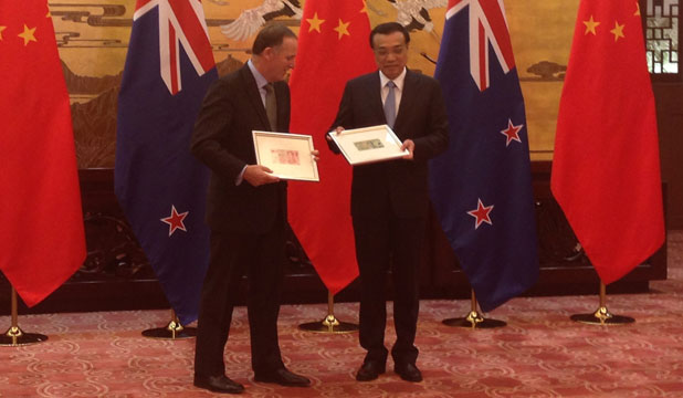DONE DEAL: John Key and Chinese Premier Li Keqiang, at the Great Hall of the People in Beijing, trade specially selected banknotes.