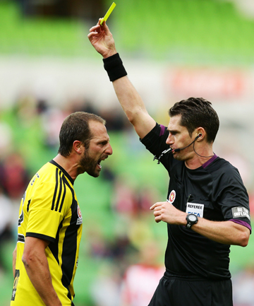 Phoenix captain Andrew Durante argues with referee Ben Williams and is given a yellow card during match with Melbourne Heart.
