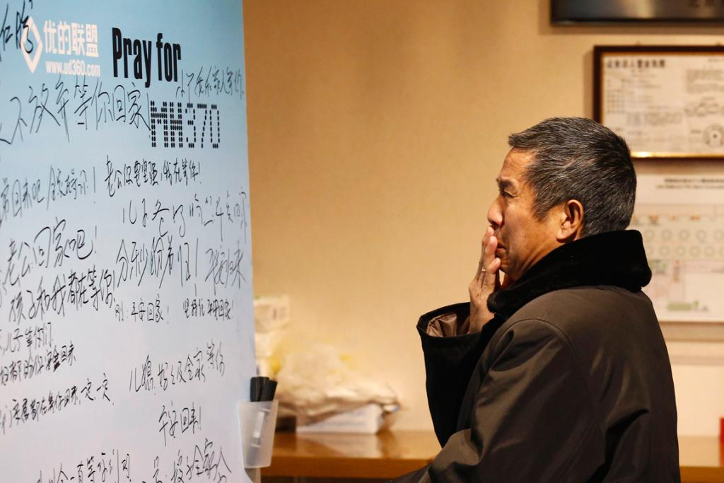 A family member of a passenger onboard the missing Malaysia Airlines flight MH370 cries as he watches a message board dedicated to passengers.