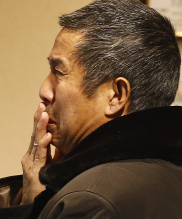GRIEVING: A relative of a person on the missing Malaysia Airlines plane cries.