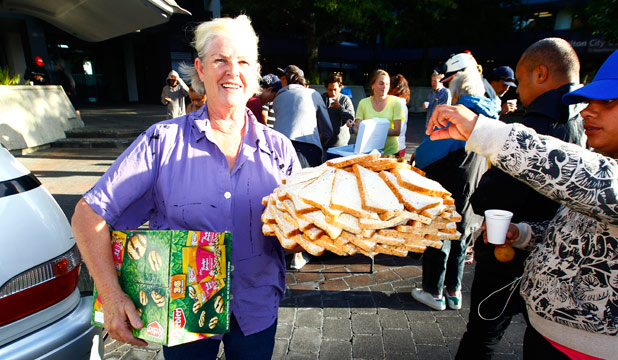 WELCOME BY SOME: Kim Forrest helps dole out dinner to hungry people in Garden Place.