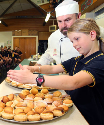 BLAST FROM THE PAST: Waihopai School pupil Rhylee Akeroyd, 10, assists Southland Boys' High School catering and hospitality teacher Scott Richardson with the dusting on some old-style cheesecakes for World Home Economics Day yesterday.