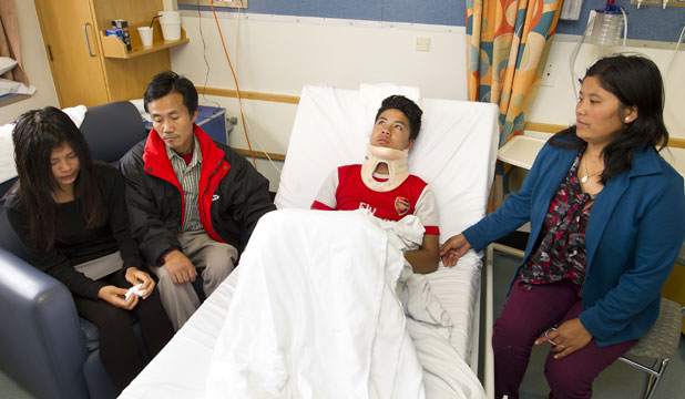 TROUBLED FAMILY: Joseph Nawl, 15,  in Wellington Hospital with a suspected broken neck. With him are sister Hlawn Nawl, 17, father Khua Kam Thang Nawl, and mother Far Can Uk.