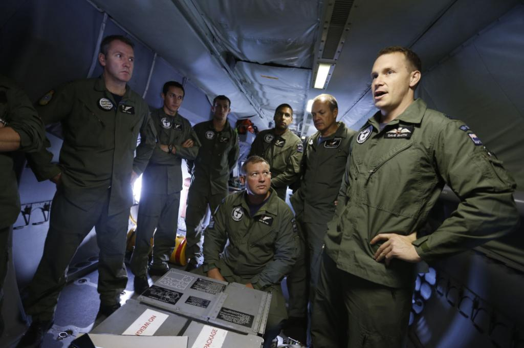 Pilot Dave Smith (R) gives a pre-flight briefing aboard a Royal New Zealand Air Force P-3K2 Orion aircraft before taking off to search for missing Malaysian Airlines flight MH370, at RAAF base Pearce near Perth, March 22, 2014.